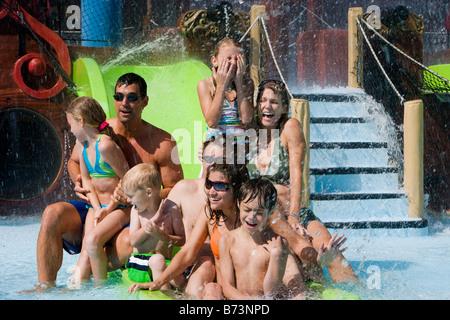 Portrait de famille jouissant sur toboggan dans l'eau park Banque D'Images