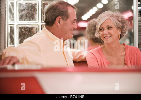 Senior couple sitting in restaurant booth parle Banque D'Images