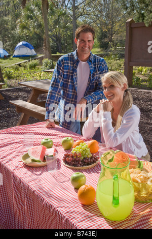 Mid-adult couple at picnic table près de camping Banque D'Images
