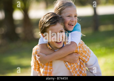 Boy giving piggyback ride à girl in park Banque D'Images