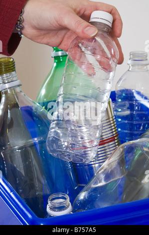 L'ajout d'aide familiale à la blue box plein de bouteilles et boîtes de recyclage Banque D'Images