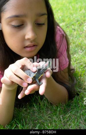 Fillette de huit ans couché dans l'herbe avec tortue, Winnipeg, Canada Banque D'Images