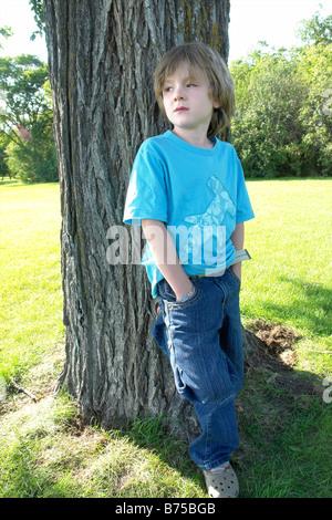 Un garçon de six ans avec les mains dans les poches se situe à côté de l'arbre, Winnipeg, Canada Banque D'Images