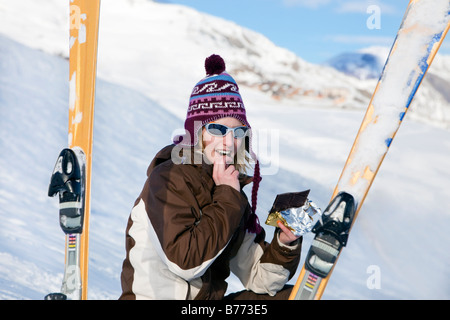 Young woman eating chocolate bar sur la neige