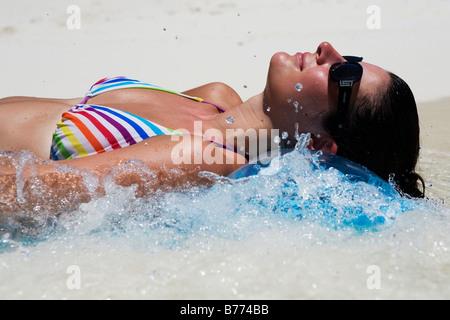 Un modèle se détend sur un lilo dans l'océan Banque D'Images