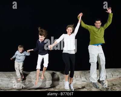 Family Jumping off driftwood Banque D'Images