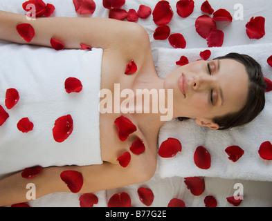 Recouverte de pose de pétales de fleur sur la table de massage Banque D'Images