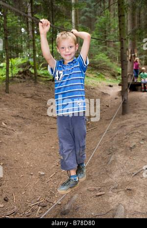 6-année-vieux garçon en équilibre sur une corde dans une forêt Banque D'Images