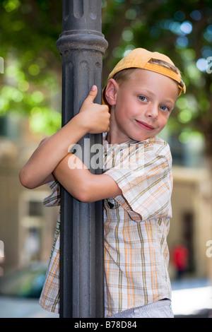 6-année-vieux garçon escalade d'un lampadaire Banque D'Images