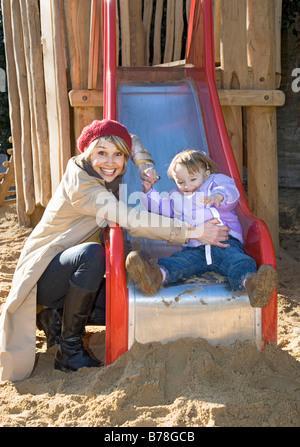 Mère et sa fille de 2 ans sur une diapositive, aire de jeux, Zurich, Switzerland, Europe