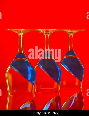 L'envers trois verres à vin avec contenu en pente bleu sur un fond rouge. Banque D'Images
