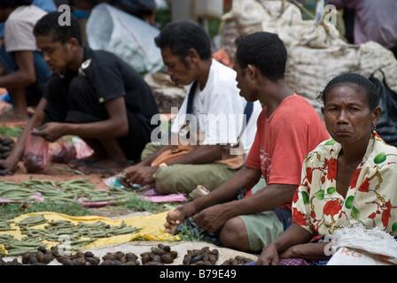 Asseoir les vendeurs à Kapan marché avec l'un d'entre eux à la désapprobation, au Timor occidental, en Indonésie Banque D'Images