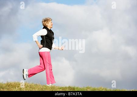 Senior Woman Jogging dans le parc Banque D'Images