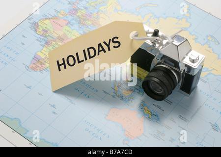 Appareil photo sur carte du monde avec 'vacances' tag
