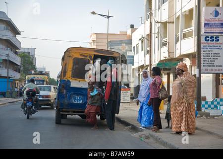 Riders descendent d'un bus à Dakar, Sénégal. Banque D'Images