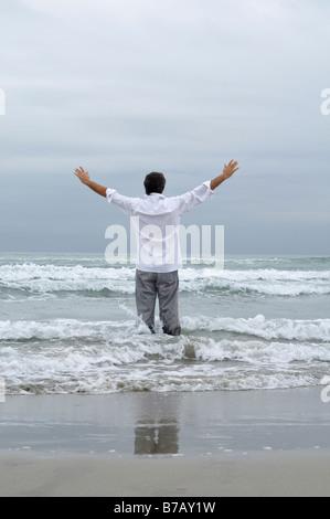 Homme debout dans les vagues sur la plage