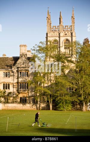 Groundsman coupe l'herbe à côté de terrain de cricket de Merton College, Oxford, Angleterre, Royaume-Uni. Banque D'Images