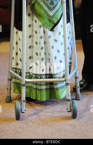 Une vieille dame Sikh est aidé à sa chaise dans un contexte multiculturel de soin supplémentaire accueil Bradford Banque D'Images