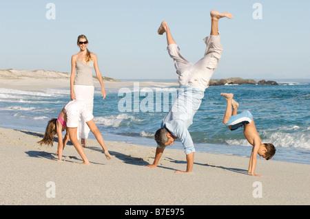 Faisant de la famille handstands sur la plage Banque D'Images