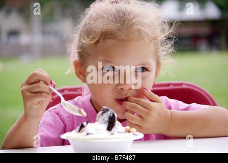 Une fillette de quatre ans biracial mange un bol de crème glacée à un pique-nique. Banque D'Images