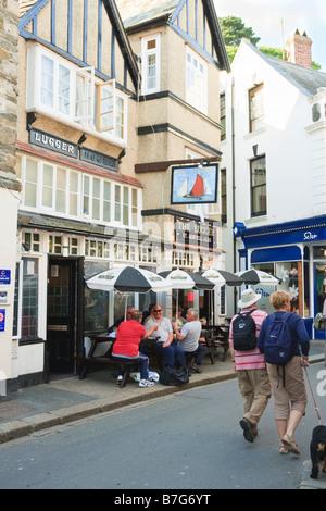 La ligne d'un pub à Fowey avec grands buveurs assis à l'extérieur et deux passants avec chien Banque D'Images