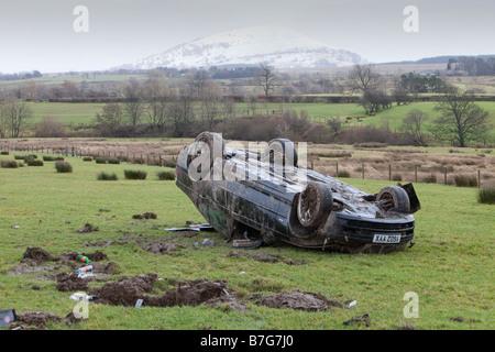 Une voiture de BMW s'est écrasé sur le toit, au milieu d'un champ après avoir quitté la route à grande vitesse sur Banque D'Images