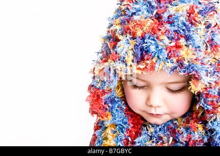 Cute baby girl un hiver chaud chapeau et un foulard coloré sur un fond  brun  Jeune femme avec capuche et écharpe colorée Banque D Images f8ba3d38b76