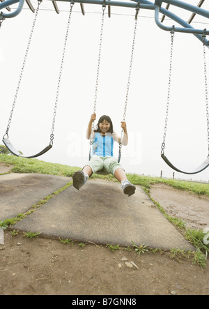 Girl sitting in a swing Banque D'Images
