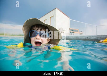 Mixed Race girl wearing sunglasses in swimming pool Banque D'Images