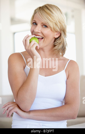 Mid adult Woman Eating Apple Banque D'Images