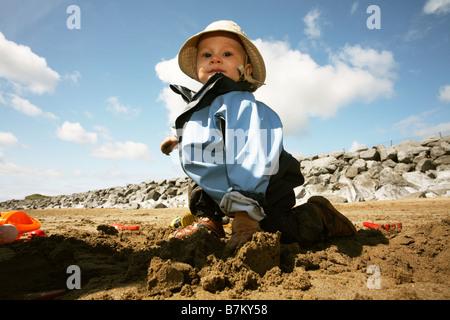 Bébé jouant sur la plage dans le sable humide. Le port de cagoule et hat. Banque D'Images
