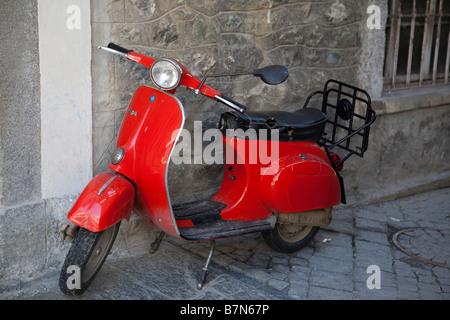 Scooter Vespa rouge garée dans une rue étroite à Bormio, Italie Banque D'Images