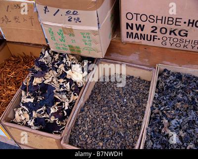 Les produits séchés dans des boîtes d'affichage en face d'une petite épicerie dans le quartier chinois de New York. Banque D'Images