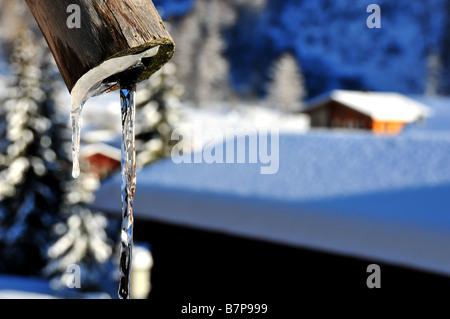 Verser de l'eau d'une fontaine gelée dans les Alpes suisses Banque D'Images