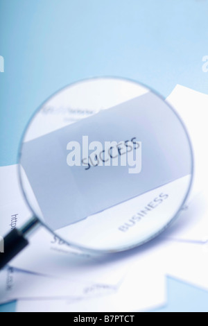 Loupe soulignant mot succès sur feuille de papier blanc Banque D'Images