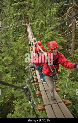 Les visiteurs marchent sur un pont suspendu dans le sanctuaire de la forêt tropicale de l'Alaska, près de Ketchikan, Banque D'Images