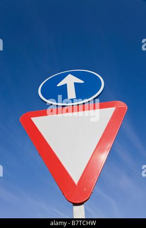 Deux panneaux de circulation: céder et tout droit Banque D'Images