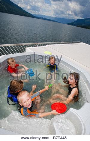 Enfants jouant dans un bain à remous sur le pont péniche Banque D'Images