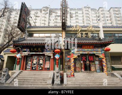 Le contraste entre les vieux bâtiments ornés avec restaurants et bâtiments appartement moderne à l'arrière au centre de Pékin.