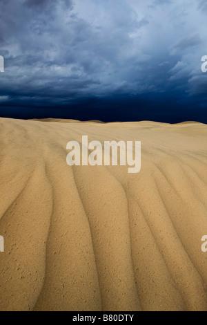 Ondulations dans le sable sur le dessus de l'augmentation des Dunes fauves près de 100 pieds de Mesquite Flat avec des nuages menaçants au-dessus