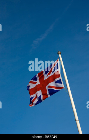 Union Jack flag flying sur mât contre le ciel bleu Banque D'Images