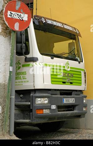 Un camion tire à travers une rue étroite, Granada, Espagne. Banque D'Images