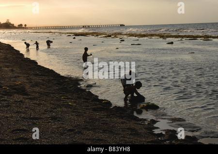 Enfants jouant dans la mer après le coucher du soleil sur la plage à Dili au Timor oriental