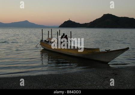 Un bateau amarré sur le port de Dili au Timor Leste avec la silhouette d'Azur Fatucama