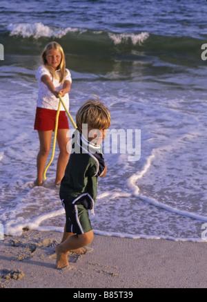Garçon Fille s'amusant avec une corde beach Banque D'Images
