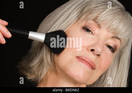 Senior woman applying make up Banque D'Images