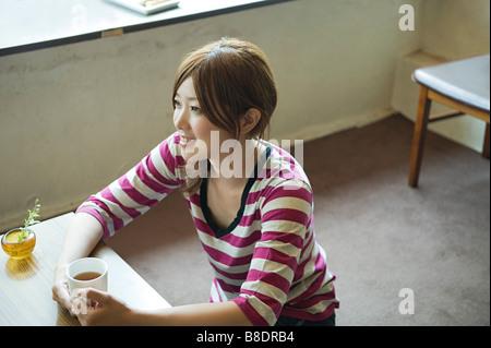 Jeune femme prenant le thé