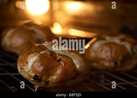 Trois les brioches assis sur un plateau grill dans le four qui est chauffé, Banque D'Images