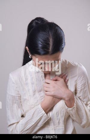Jeune femme mains sur coeur Banque D'Images