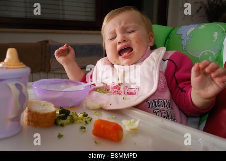 Un an bébé fille pleurer dans une chaise haute à l'heure des repas Banque D'Images